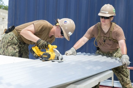 Image of a male and female, both in construction, working on the job.